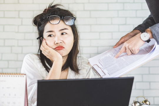 tired and bored female Asian employee ignore annoying boss at office desk