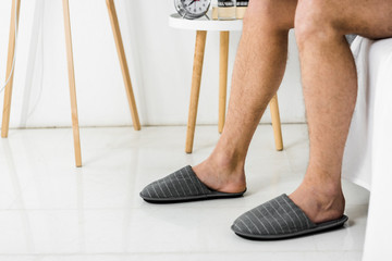 cropped view on male legs in slippers in bedroom