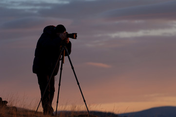 Photographer's silhouette early in the morning at sunrise carefully focusing and composing photos with his digital camera set on a tripod.