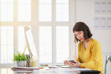 Young woman working in office, sitting at desk, using computer.