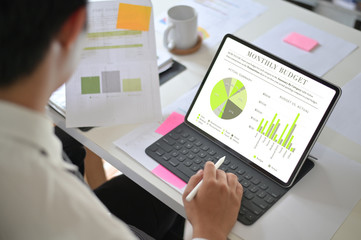 Businessman analyzing financial statistics displayed on the tablet screen.