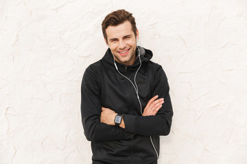 Image of athletic sportsman 30s in black sportswear and earphones, standing over white wall outdoor Wall mural