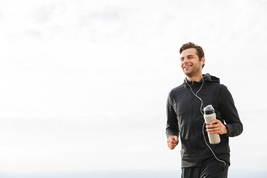 Image of adult sportsman 30s in black sportswear and earphones, working out and running by seaside