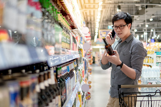 Asian man using phone shopping beer in supermarket. Male shopper with shopping cart choosing beer bottle in grocery store.