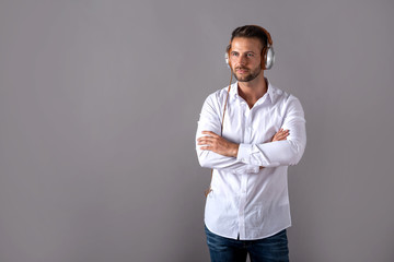 A serious handsome young man in a white shirt listening to music on his headphones and standing in front of a grey background in the studio.