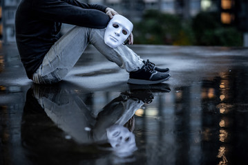 Reflection of mystery man with black jacket holding white mask sitting in the rain on rooftop of abandoned building. Bipolar disorder or Major depressive disorder. Depression concept
