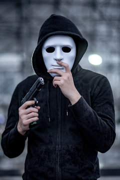 Mystery hoodie man in white mask holding gun. Crime and violence concepts