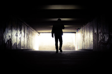 A man going to the end of a tunnel to the light. Silhouette of a man going to light in the end of a tunnel.