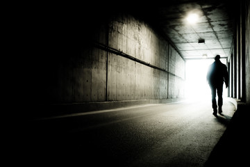 A man going to the end of a tunnel to the light. Silhouette of a man going to light in the end of a tunnel. Fotomurales