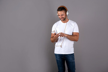 A smiling handsome young man in a white shirt listening to music on his headphones and holding his smartphone while standing in front of a grey background in the studio.