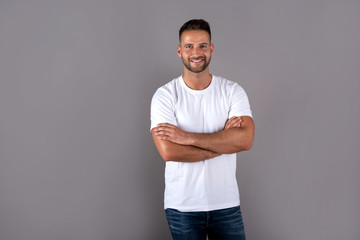 A smiling handsome young man in a white tshirt standing in front of a grey background in the studio.