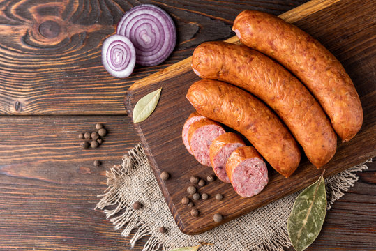 Smoked sausage with spices and onion on wooden background.