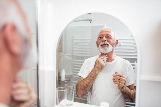 Handsome senior man looking at mirror in the bathroom.