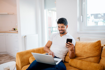 Young smiling african american man using laptop and mobile phone while sitting on sofa.