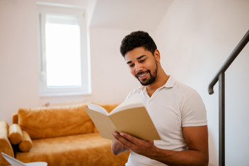 Portrait of a smiling mixed-race man reading a book at home.
