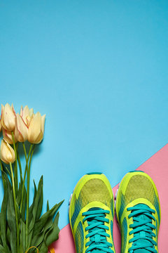 Pair of sport shoes and yellow tulips bouquet on colorful pastel background. New sneakers on pink and blue paper, copy space. Overhead shot of running foot wear. Top view, flat lay