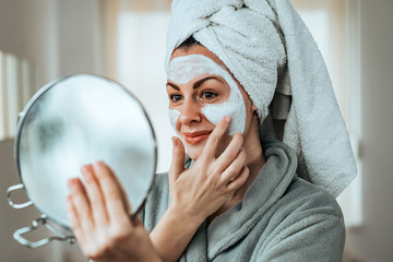 Beautiful woman with facial mask or cream at home.