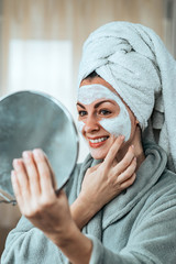 Charming woman holding mirror and applying cream after bath.