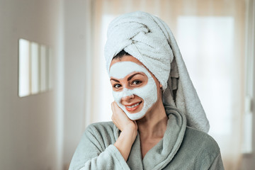 Charming young woman with facial mask, in bathrobe, standing and looking at camera.