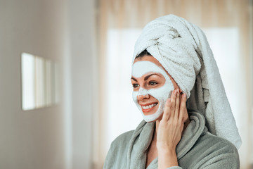 Portrait of a beautiful young woman in bathrobe and towel with facial mask.