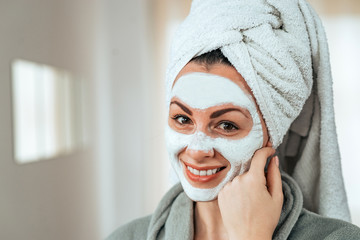 Head shot of a beautiful smiling woman with facial mask.