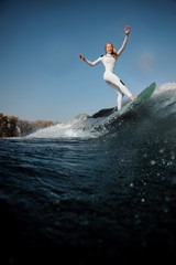 Side view blonde girl standing on the wakeboard