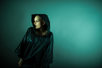 Emotive photo of a beautiful bald woman in a black raincoat with the hoods on.