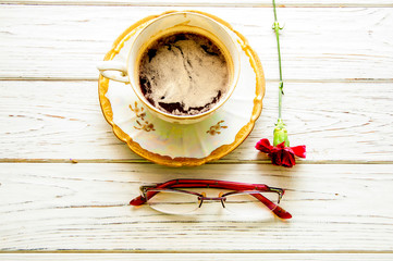 Cup of coffee, red carnation, glasses on a light wooden background. view from above