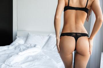 Brunette woman wearing lingerie posing in bedroom.