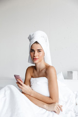 Beautiful young woman wrapped in bath towel