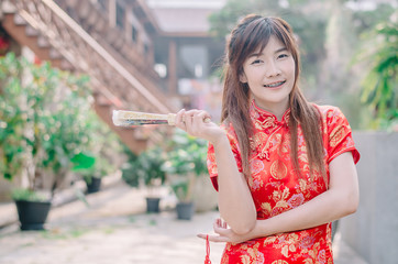 Portrait beautiful young woman smile wear cheongsam deep red dress holding a fan looking camera. Festivities and Celebration concept