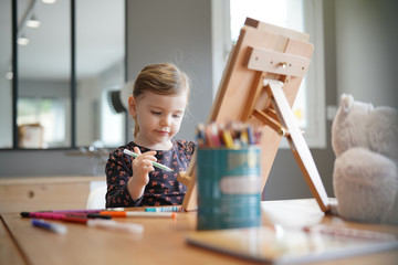 Young girl drawing by herself on easel at home