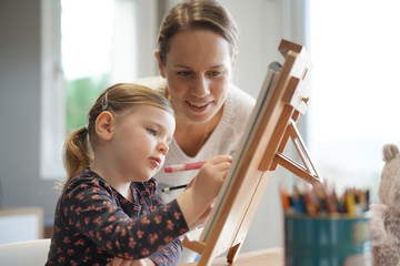 Mother and young daughter drawing together at home on easel