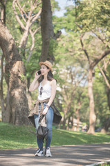 Beautiful asian solo tourist woman  smiling and enjoy taking via mobile phone while walking in public nature park. Vacation travel in summer.