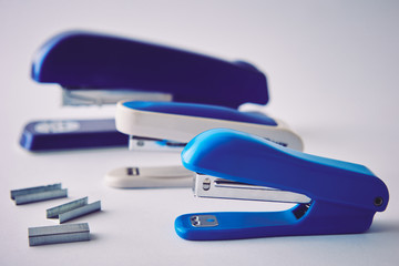Three staplers on a white background, close-up