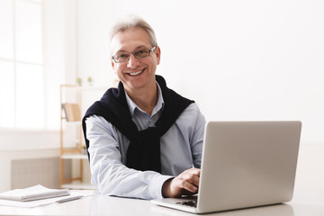 Senior man using computer and looking at camera