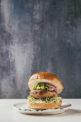 Homemade vegan vegetarian burger in wheat bun with portobello mushroom, avocado salsa and sprouts on white ceramic plate over white marble table.