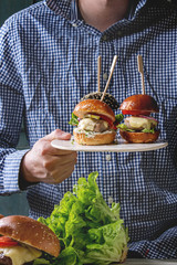 Man in blue shirt holding in hands homemade classic and mini burgers in wheat and black buns with beef cutlets, melted cheese, vegetables on white ceramic board. Table with ingredients in foreground.