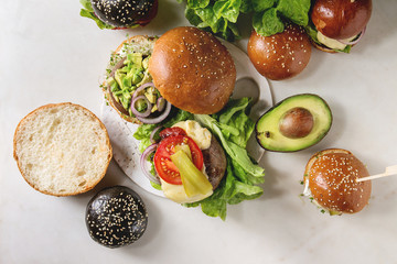 Variety of homemade classic, vegan and mini burgers in wheat and black buns with beef and veal cutlets, portobello mushroom, avocado, melted cheese and vegetables on white marble table.