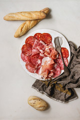 Antipasto meat platter assorti of sliced jamon, salami, chorizo sausage on white ceramic board with bread on cloth over white marble background. Flat lay, space