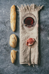 Antipasto meat sliced jamon on fork with artisan bread variety and glass of red wine on cloth over blue texture background. Flat lay, space. Appetizer concept