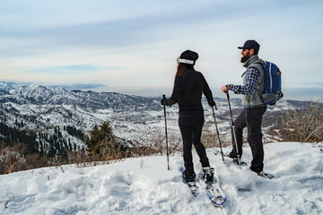 Travelers in the mountains walk on snowshoes. The guy with the girl on the edge of the hill look into the distance. Winter mountain tourism