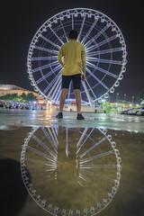 Young man looking Ferris wheel at night market Asiatique ,Bangkok Thailand