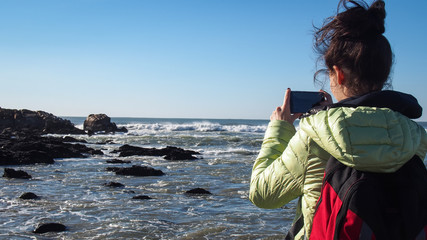 Turist girl taking photo by phone of the stormy ocean with rocks