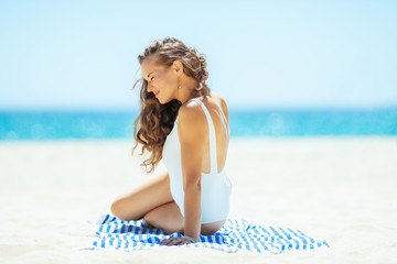 relaxed young woman on ocean shore siting on striped towel