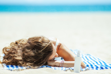 healthy woman with suntan lotion laying on striped towel