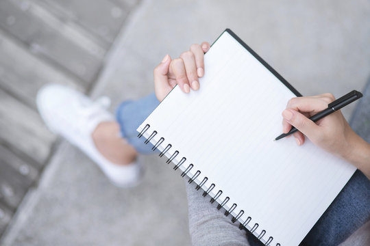 Top view female hands with pen writing on notebook notepad sitting in public park outdoor. Leave copy space  empty write a message.