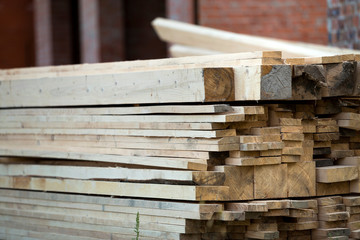 Stack of natural brown uneven rough wooden boards on building site. Industrial timber for carpentry, building, repairing and furniture, lumber material for roofing construction.