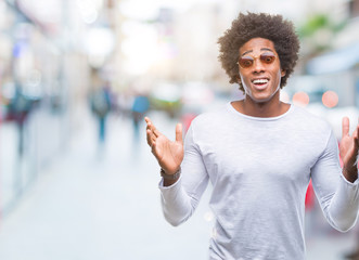 Afro american man wearing sunglasses over isolated background crazy and mad shouting and yelling with aggressive expression and arms raised. Frustration concept.