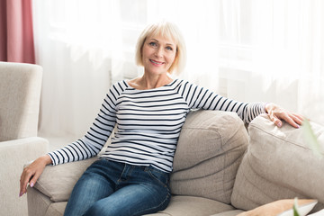 Cheerful senior woman feeling happy and relaxed, sitting on couch